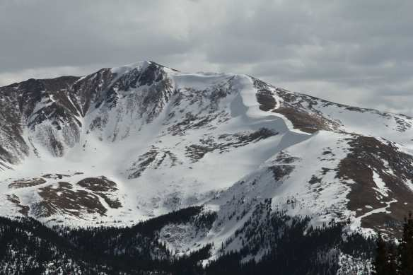 Cornices are created when the wind picks up snow on one side of a ridge and drops it on the far side. The wind then packs the snow down.